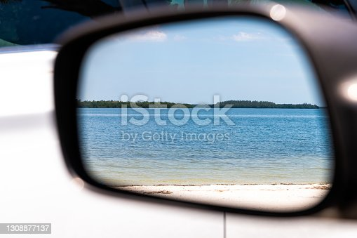 istock Car window side mirror with reflection at Fort Myers Beach by Sanibel island with landscape bay water ocean sea view in Florida, Gulf of Mexico 1308877137