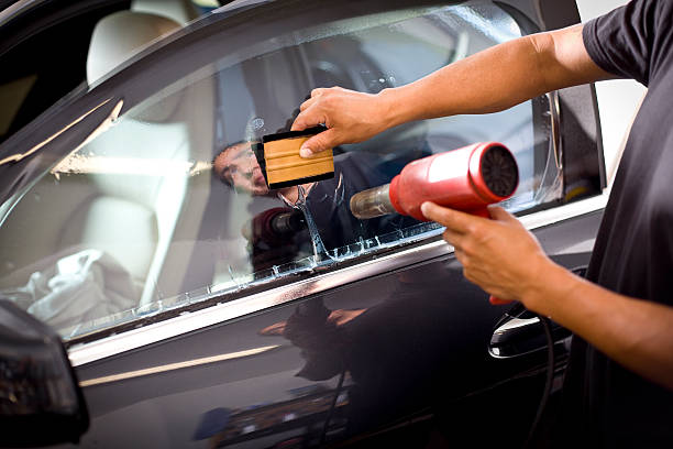 Car Window Tinting Man installing window tinting on car. toned image stock pictures, royalty-free photos & images