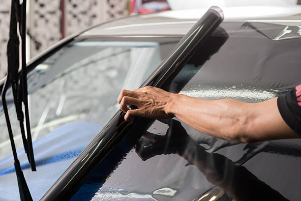 Car window tinting series : Installing car window tint Installing car window tint toned image stock pictures, royalty-free photos & images
