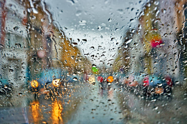 Car windshield with rain drops during storm and blurred stoplights stock photo