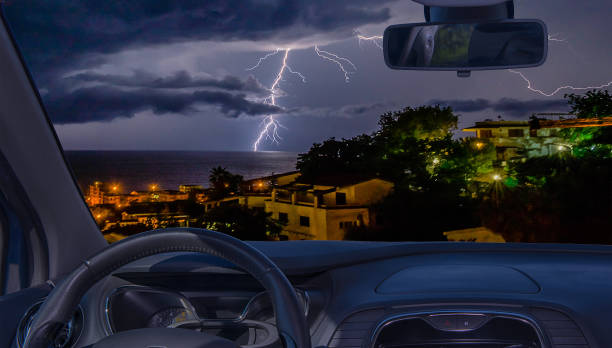 Car windshield with view of lightning storm over the sea - foto stock