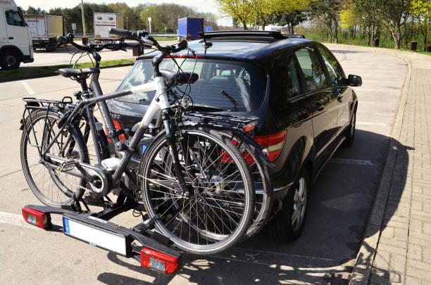 auto mit einem fahrradträger und zwei fahrräder auf einem autobahn-rastplatz - fahrradhalter stock-fotos und bilder