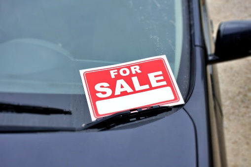 A For Sale sign in a car window.