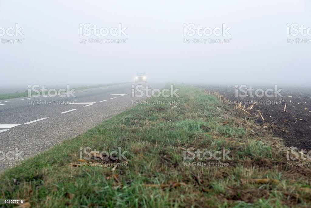 Car with headlights driving on misty rural road. photo libre de droits