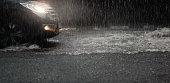 Car with headlights run through flood water after hard rain fall at night.Rainy season.