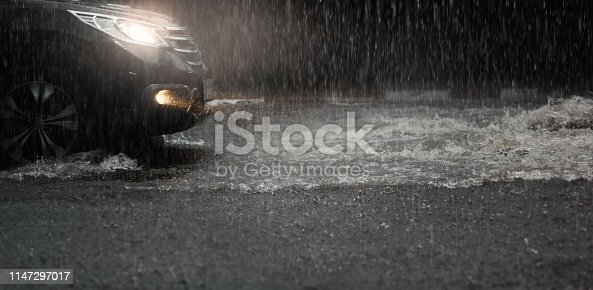Car with headlights run through flood water after hard rain fall at night.Rainy season.