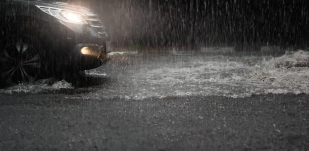 samochód z reflektorami biegnie przez wodę powodziową po ulewnym deszczu w nocy. - deszcz zdjęcia i obrazy z banku zdjęć