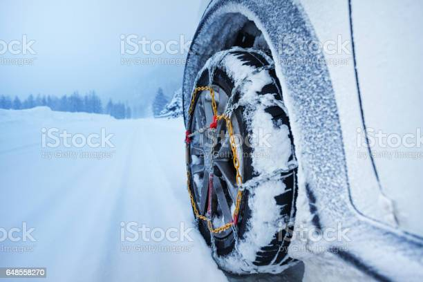 Photo of Car with snow chains for tire on snowcapped road