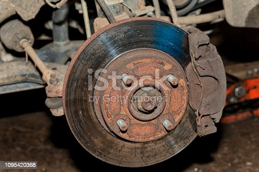 A car with the front wheel removed where you can see the brake disc.