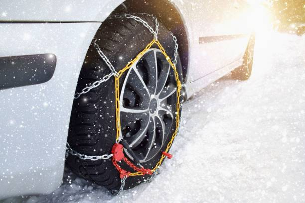 auto met banden kettingen in de winter - tractieapparaat stockfoto's en -beelden