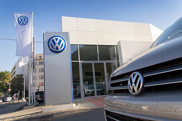 Auto mit einem VW-Autohaus auf der Vorderseite des Gebäudes – Foto