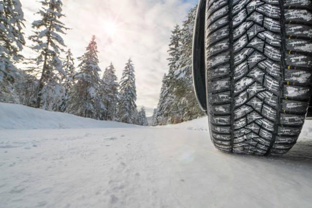 coche con neumáticos de invierno en el camino cubierto de nieve - tires fotografías e imágenes de stock