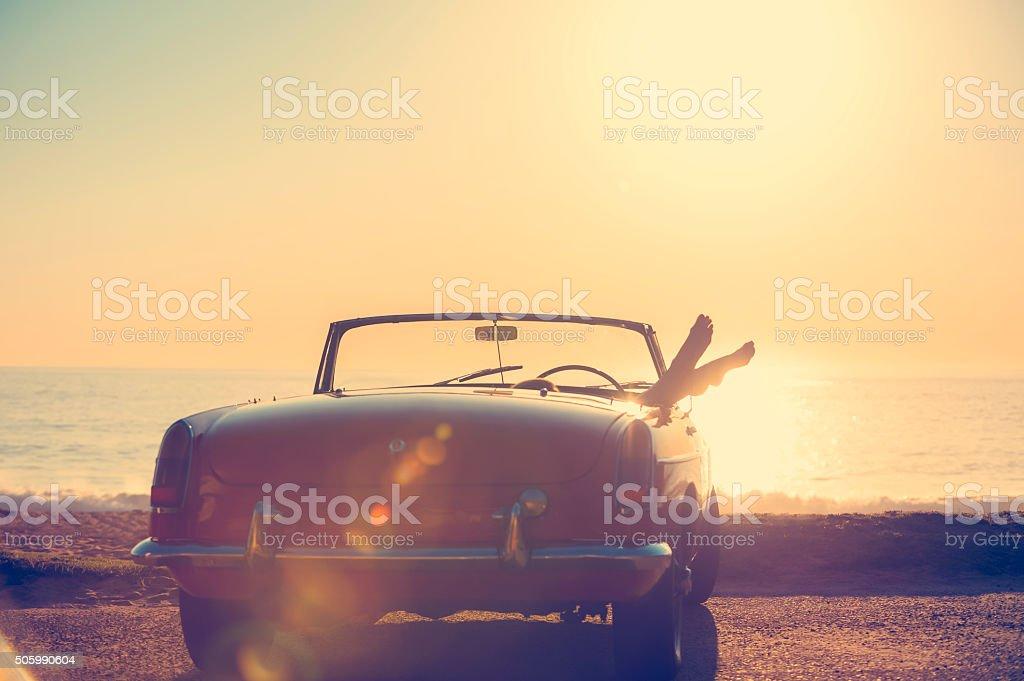 Auto mit Frau Füße hängende aus dem Fenster. – Foto
