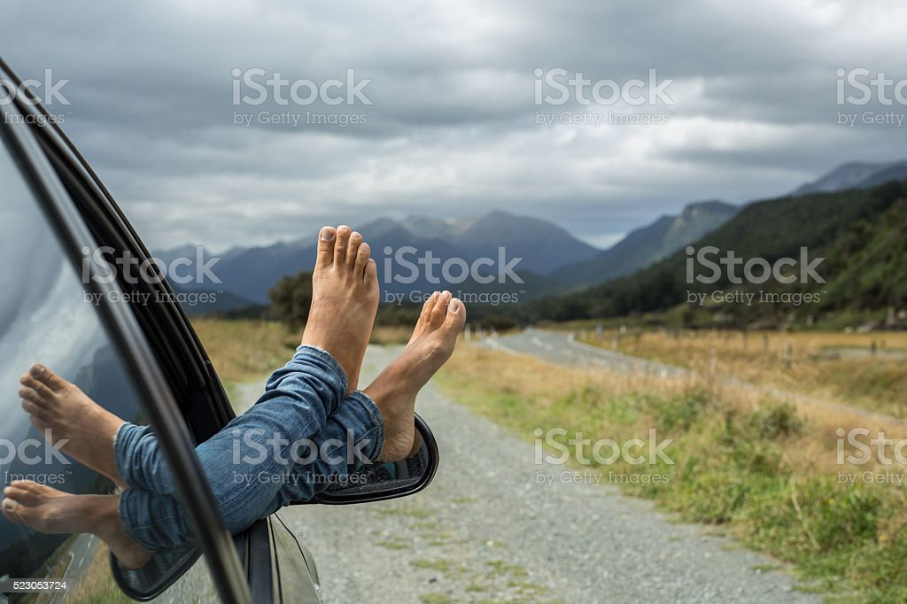 Car with woman's feet hanging out of the window stock photo