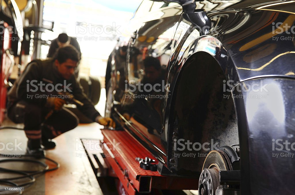 Car without wheel in repair shop stock photo