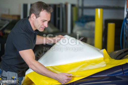 istock Car wrapper preparing foil to wrap a vehicle 489271351