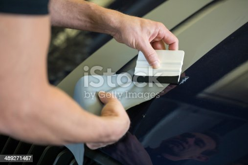 istock Car wrapper straightening foil with a squeegee 489271467