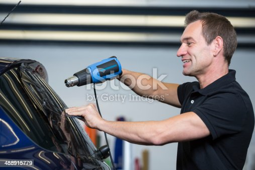 istock Car wrapper using heat gun and squegee for tinting window 488915779