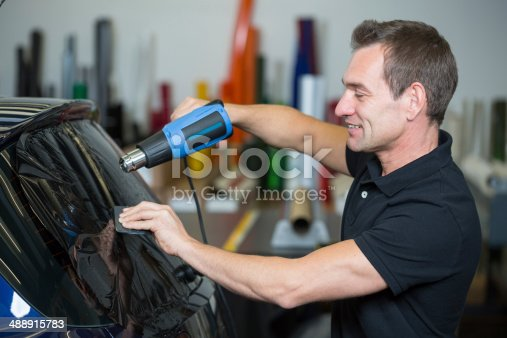 istock Car wrapper using heat gun and squegee for tinting window 488915783