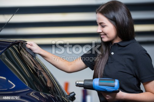 istock Car wrapper using heat gun and squegee for tinting window 488915791