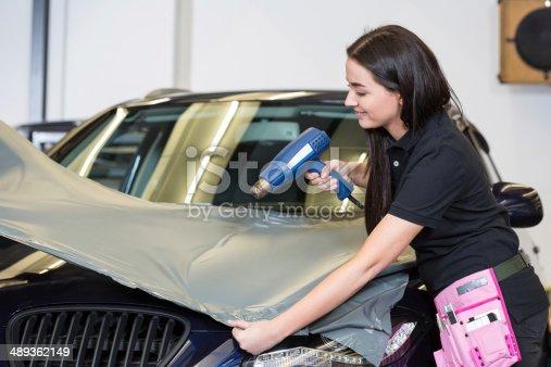 istock Car wrappers using heat gun to flatten vinyl film 489362149