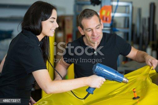 istock Car wrappers using heat gun to prepare vinyl foil 489273317