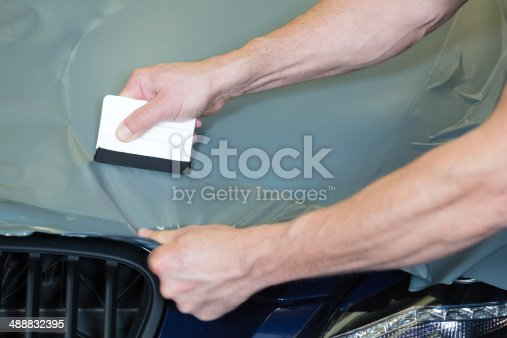istock Car wrappers using squeegee to straighten vinyl film 488832395