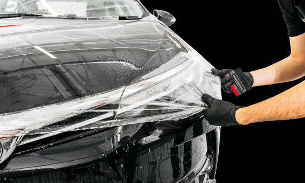Wagenverpackungsspezialist, der Vinylfolie oder Folie auf Auto legt. Schutzfilm am Auto. Mit Werkzeug eine Schutzfolie auf das Auto auftragen. Auto-Details. Transparenter Film. Lackschutz für Autos. Trimmen – Foto