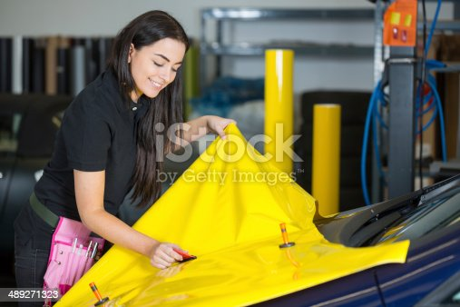 istock Car wrapping specialists straightening vinyl foil or film 489271323