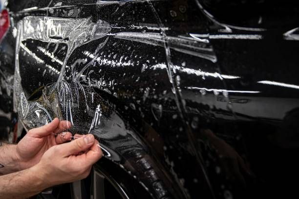 Car wrappping. Man car detailing studio worker appling transparent protection foil on car body. stock photo
