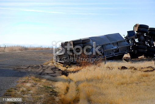 istock Car wreck of semi truck trailer rolled over crash crashed wrecked rollover 1136629203