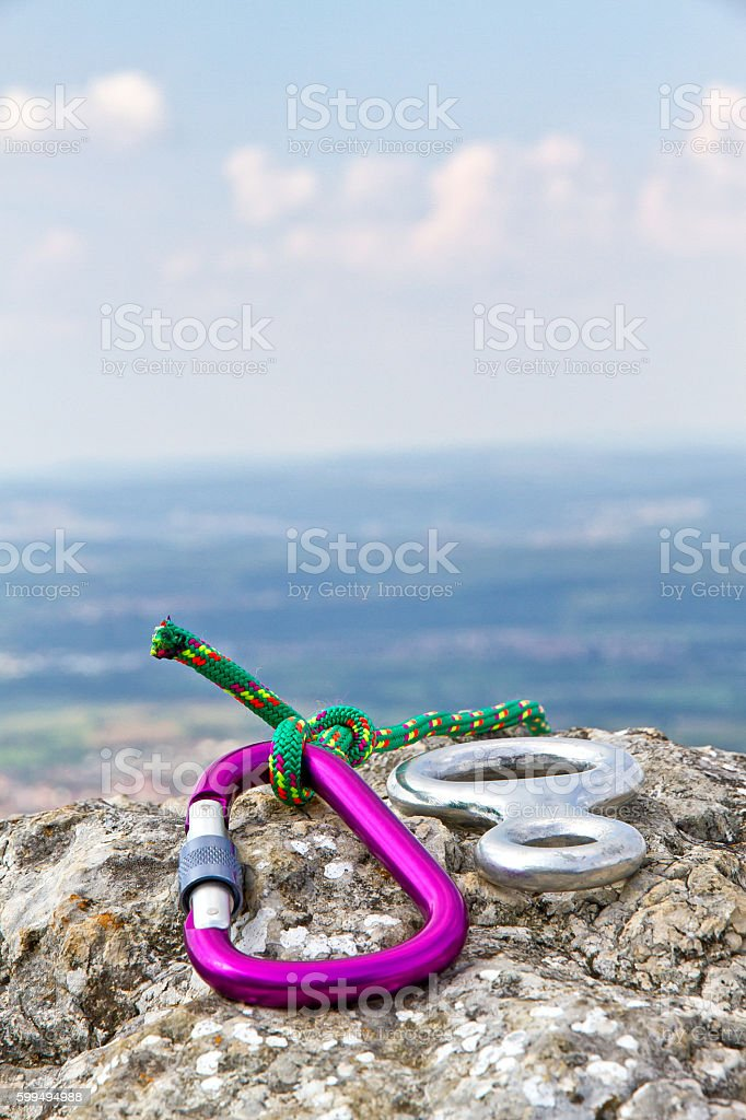 Carabiner with rope on a rock stock photo