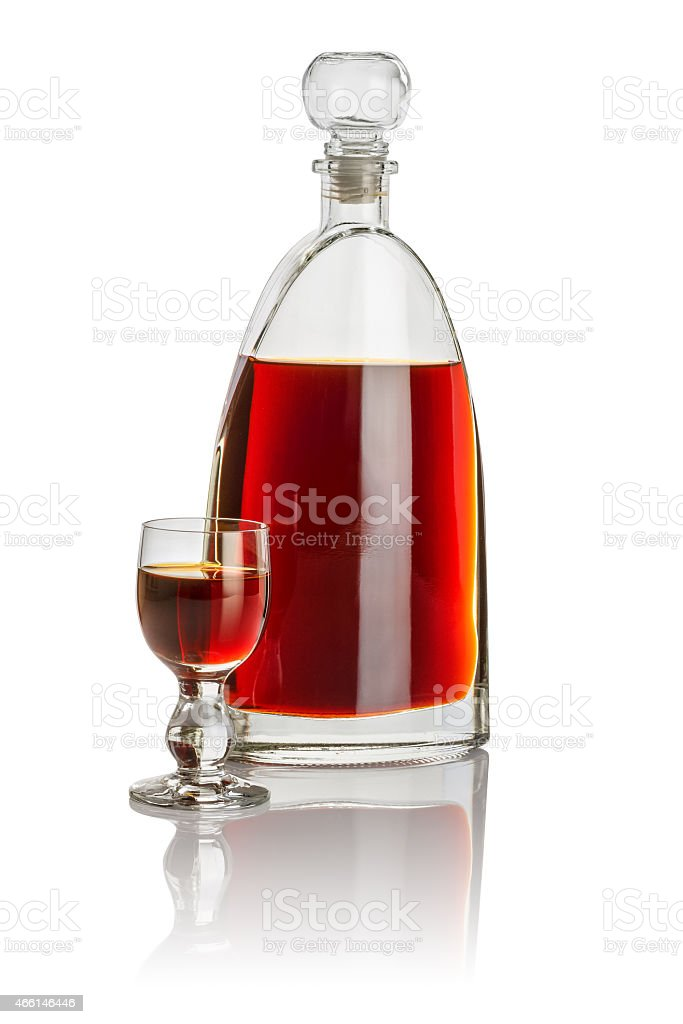 Carafe and glass goblet filled with brown liquid stock photo