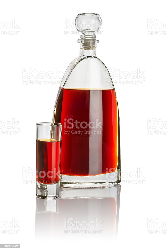 Carafe and high shot glass filled with brown liquid stock photo