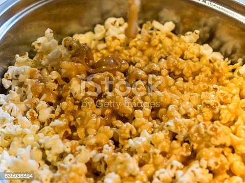 This home made Caramel Popcorn is a sweet treat very popular in North America. Photo taken close from above as caramel is being added to the popcorn.