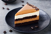 Caramel cake, mousse dessert on a plate. Grey stone background