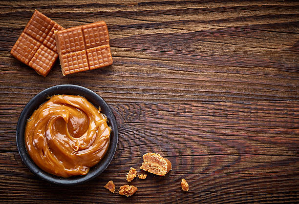 caramel candies and sweet sauce - karamel stockfoto's en -beelden