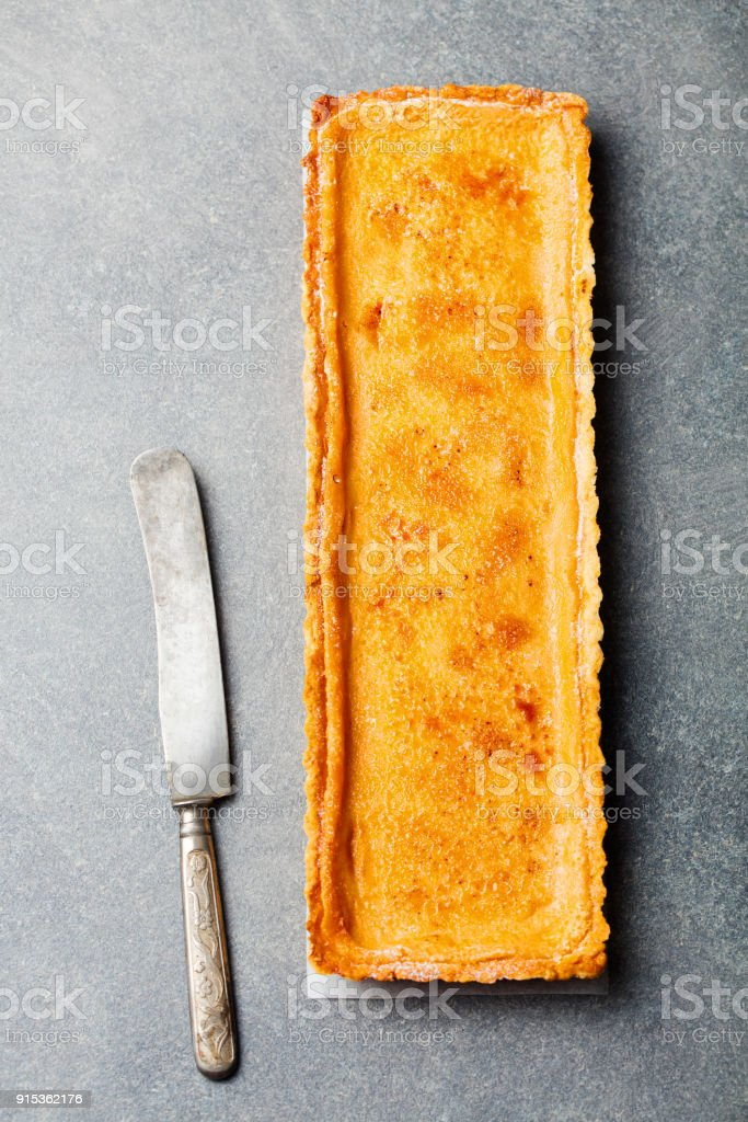 Caramel, creme brule tart. Grey stone background. Top view stock photo