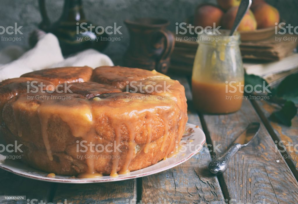Caramel monkey bread. Apple pie with brown sugar and cinnamon on a wooden background. Autumn baking. Homemade sweets. Rustic style. Copy space. stock photo