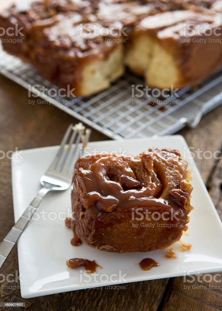 Caramel Pecan Roll on Plate with Additional Rolls in Background. stock photo