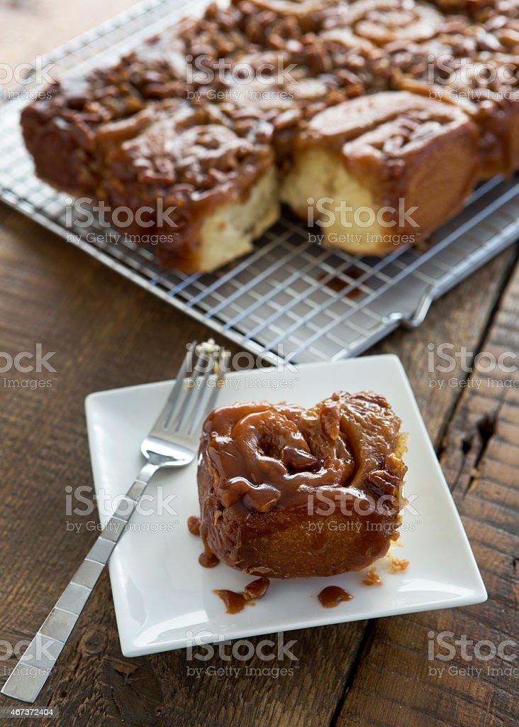 Caramel Pecan Sticky Bun on Plate Next to Cooling Rack. stock photo