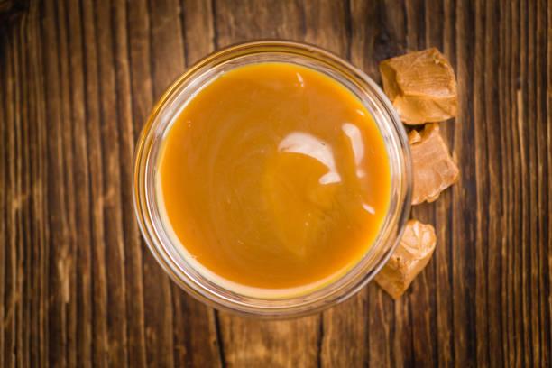 karamell-sauce auf hölzernen hintergrund (tiefenschärfe) - karamellsirup stock-fotos und bilder