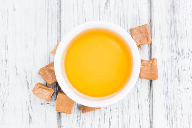 karamell-sirup auf hölzernen hintergrund (tiefenschärfe) - karamellsirup stock-fotos und bilder