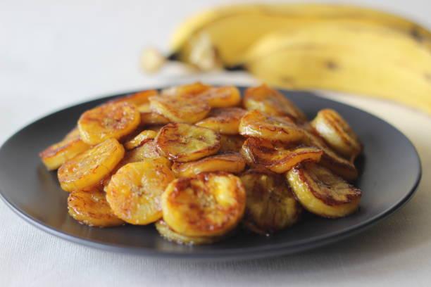 irisan pisang karamel. camilan waktu teh tradisional dari kerala.potong pisang matang menjadi irisan dan panggang dalam wajan menambahkan ghee n beberapa gula merah. - caramelized banana potret stok, foto, & gambar bebas royalti
