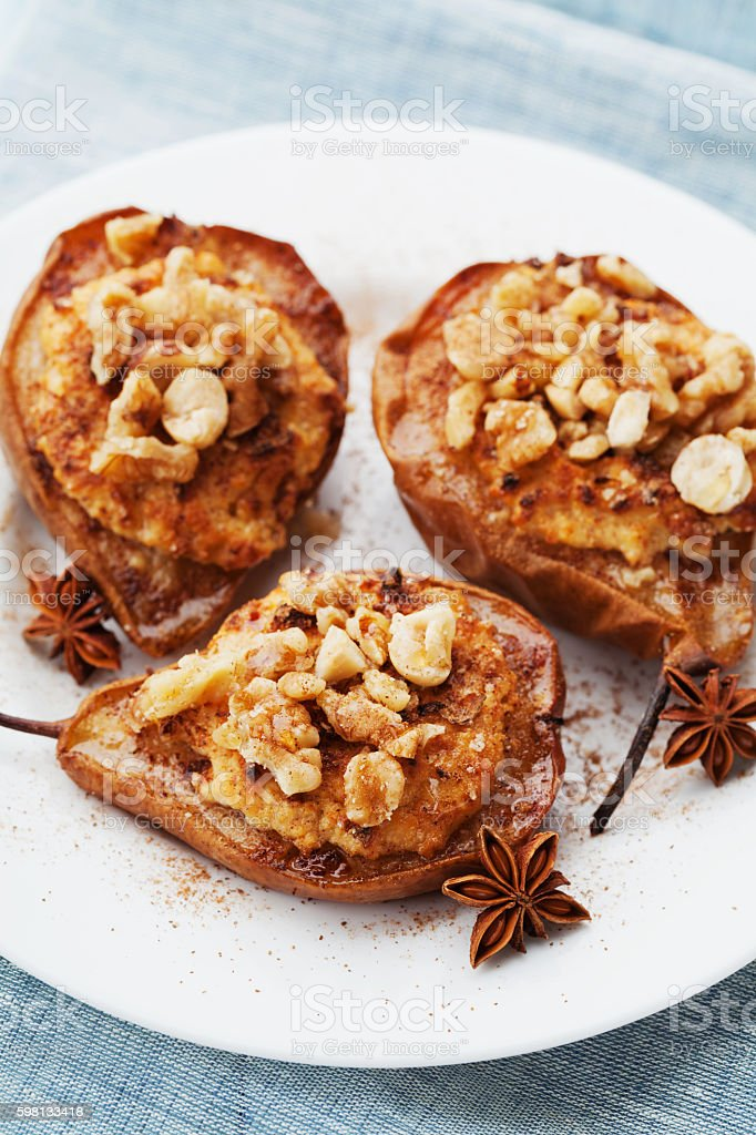 Caramelized baked pears with ricotta, walnuts, honey. Delicious autumn dessert. stock photo