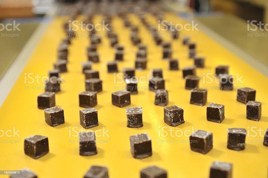 Caramels on a conveyor belt stock photo