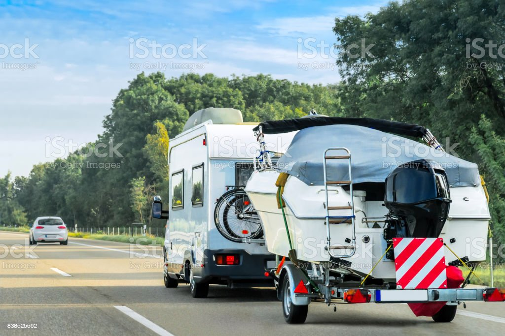 Caravan and trailer for motor boats on road in Switzerland stock photo