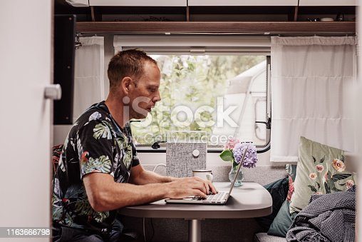 Caravan camping lifestyle  Man indoors inside a modern caravan with laptop computer and coffee