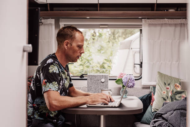 Caravan camping lifestyle Caravan camping lifestyle  Man indoors inside a modern caravan with laptop computer and coffee rv interior stock pictures, royalty-free photos & images