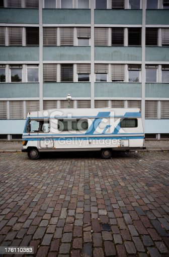 Old caravan in front of and old broken down apartment building. The apartments look like subsidized housing projects. The mood of the image is very grim and depressing.